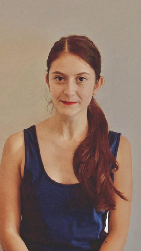 A headshot of Elena Bolelli. Elena is wearing a blue vest top and has long brown hair with a reddish tone. Her hair is in a ponytail, with the tail falling over one shoulder.